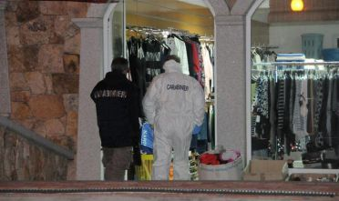 Carabinieri al lavoro all'esterno del negozio dove una donna cinese di 37 anni è stata trovata morta, Budoni (Nuoro), 10 aprile 2017. Ad ucciderla undici coltellate inferte, forse, da un ladro che ha tentato una rapina sfociata in omicidio. ANSA/MARIA GIOVANNA FOSSATI